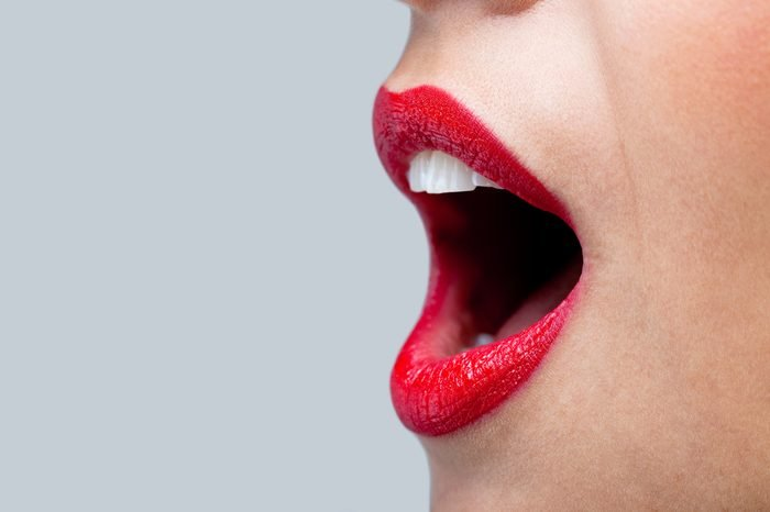 Close up of a womans mouth wide open with bright red lipstick on her lips.