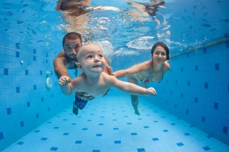 Happy full family - mother, father, baby son learn to swim, dive underwater with fun in pool to keep fit. Healthy lifestyle, active parent, people water sport activity, swimming lesson. Focus on child