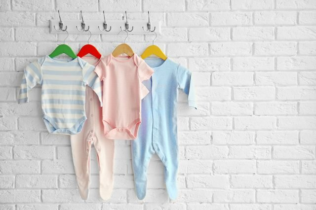 Colorful set of baby romper on brick wall