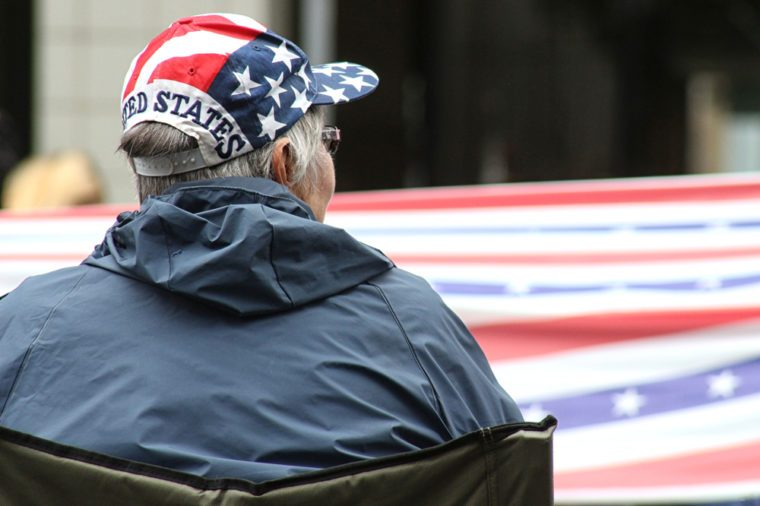 Red, white and blue hat on woman who watches the American flag go by at a July 4th parade.