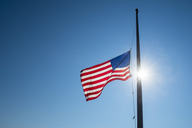 American flag lowered to half mast backlit by bright sun lens flare