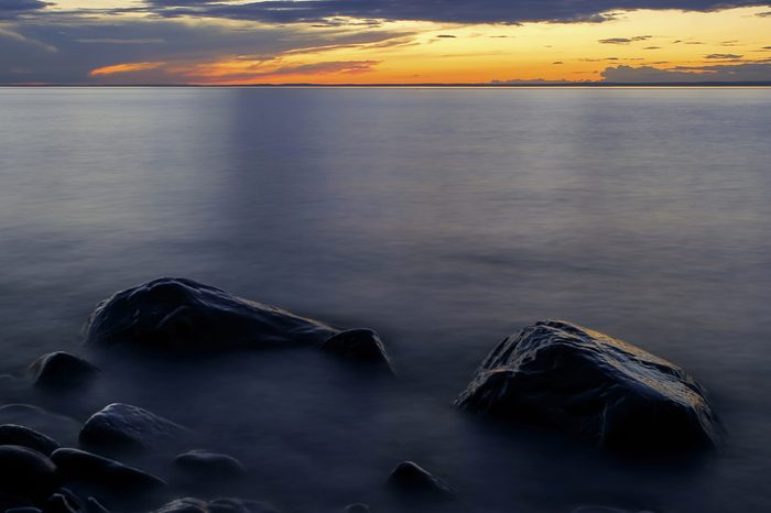 Waves Lap Around Rocks of Lake Superior's Wisconsin Shoreline During a Vibrant Sunset