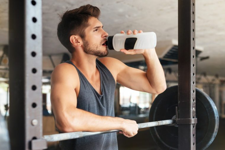 Beautiful fitness man with weights drinking water. after training
