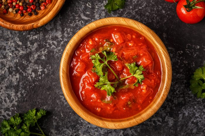 Tomato sauce with garlic and parsley in a wooden bowl, top view.