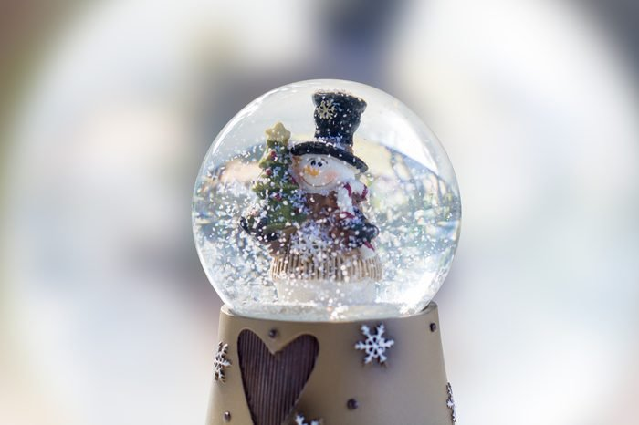 Snow globe with fir tree and cute snowman on blurred background.