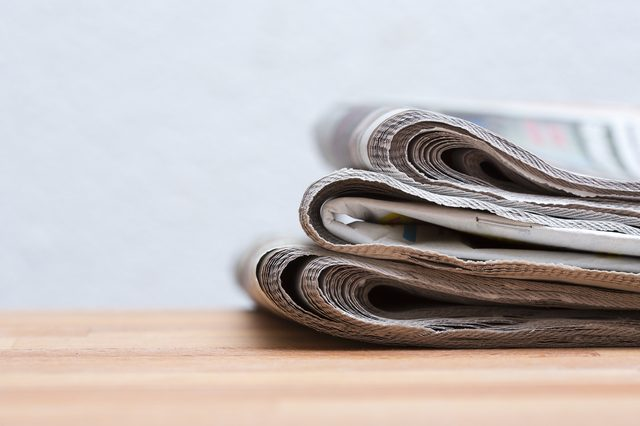 Pile of newspapers on a wooden table.