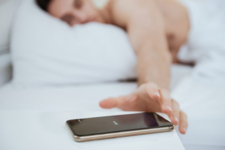 Cropped image of Man lying on bed and pulling to the phone which lying near the bed. Focus on phone