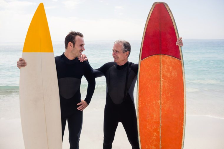 Father and son with surfboard standing on beach on a sunny day