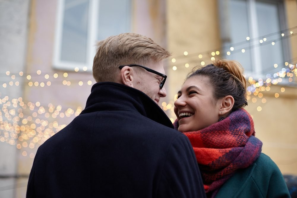 Outdoor portrait of happy smiling couple in love having fun together. Young Caucasian man with tenderness looks at his laughing Latin beloved on the background of garlands of lights