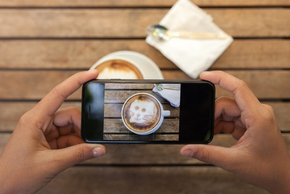 overhead view of hands holding a smartphone taking a photo of a coffee cup
