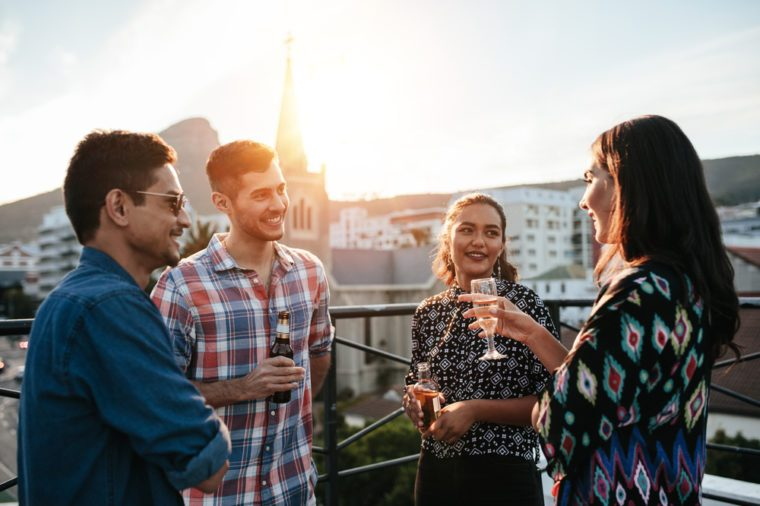 Four friends standing together on rooftop with drinks and chatting. Young men and women having a rooftop party.