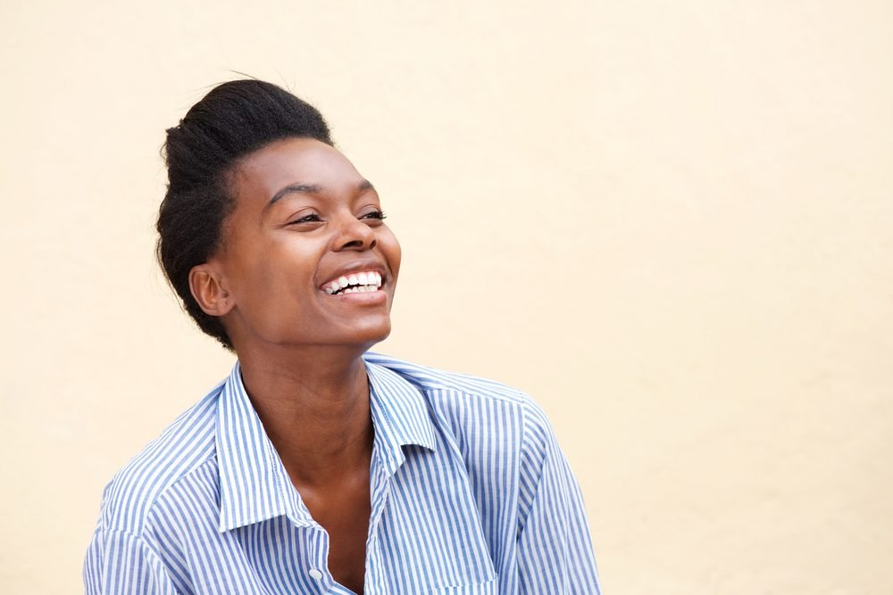 Close up portrait of beautiful young black woman laughing against wall