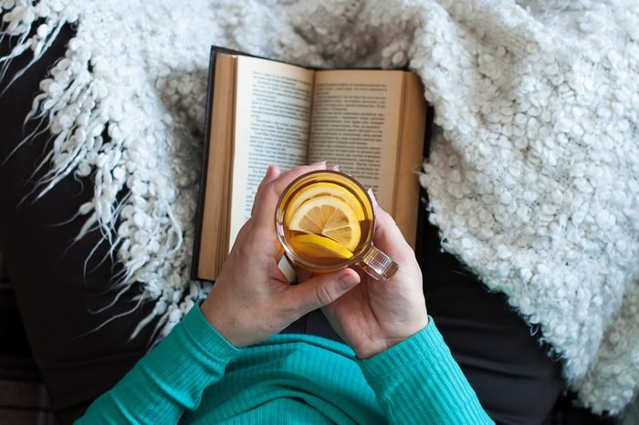 A woman is drinking tea and reading a book, female hands are holding a glass beaker with a drink. Lifestyle, relaxation