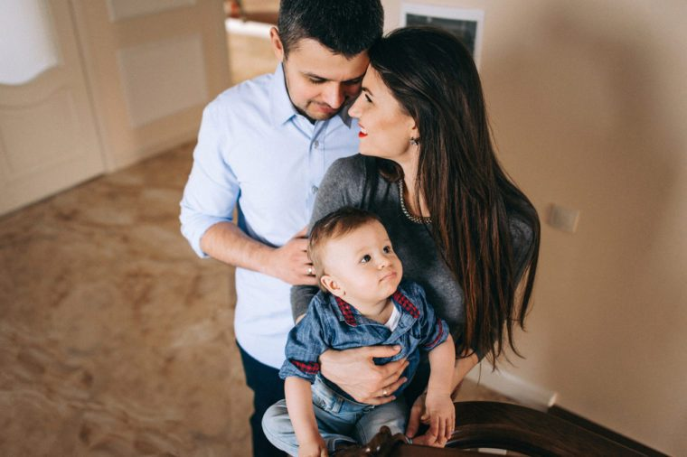 Happy family with his son in his cozy home. Mom tenderly hugs her son on the steps with railing
