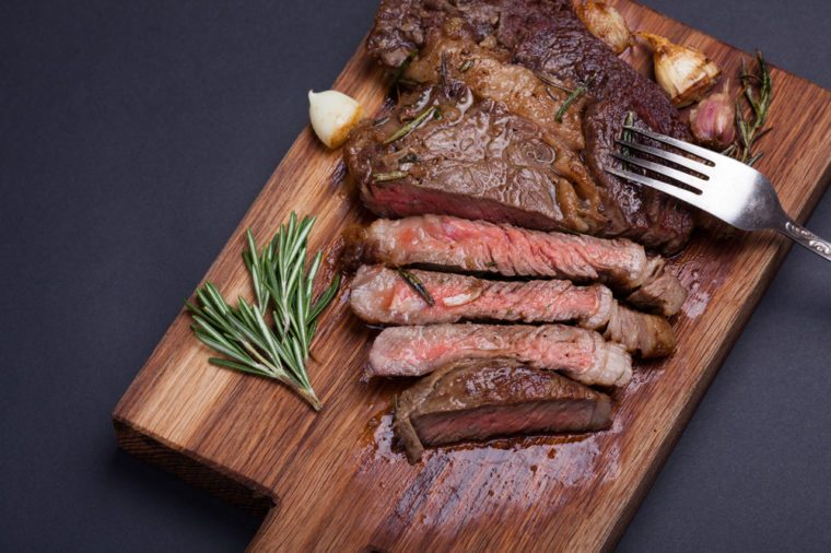 Grilled ribeye steak of marble beef closeup with spices on a wooden Board. Juicy steak medium sliced and ready to eat. Meat cow breed black Angus. With copy space. Top view.