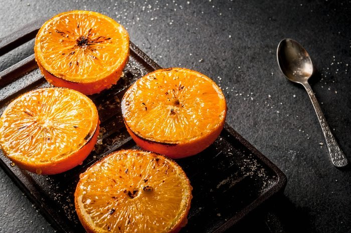 Ideas for a healthy dietary vegan breakfast. Paleo diet. Grilled oranges grapefruits. In the grill pan on a black stone table. Copy space