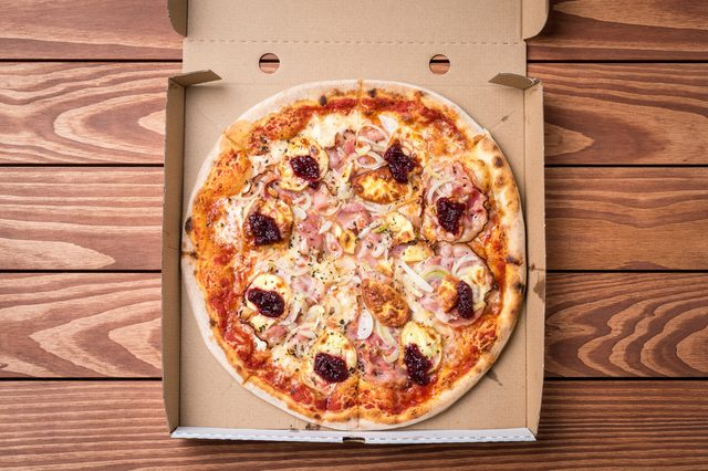 Pizza in cardboard box on wooden table