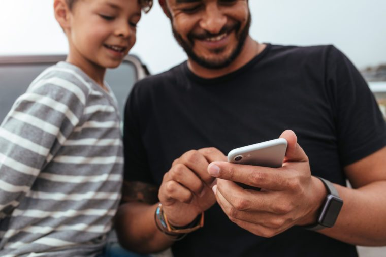 Close up of happy father and son in front of the car looking at the mobile phone. Young man and little boy using smart phone while on road trip.