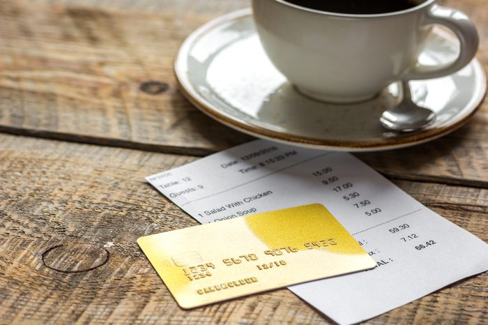 restaurant bill paying by credit card for coffee on wooden table background