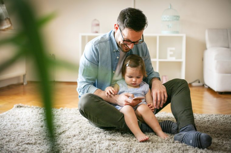 Single father wit his daughter using smart phone. Father and little baby watching something funny at smart phone.