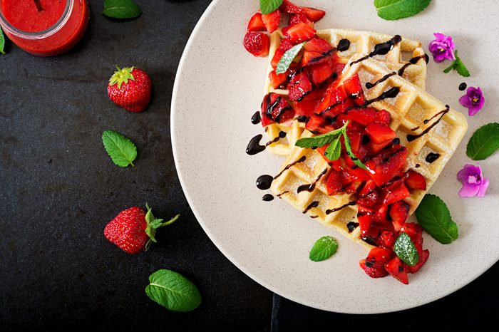 Belgium wafers with strawberries, chocolate and syrup on a plate. Flat lay. Top view