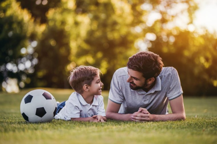 Handsome dad with his little cute sun are playing football on green grassy lawn