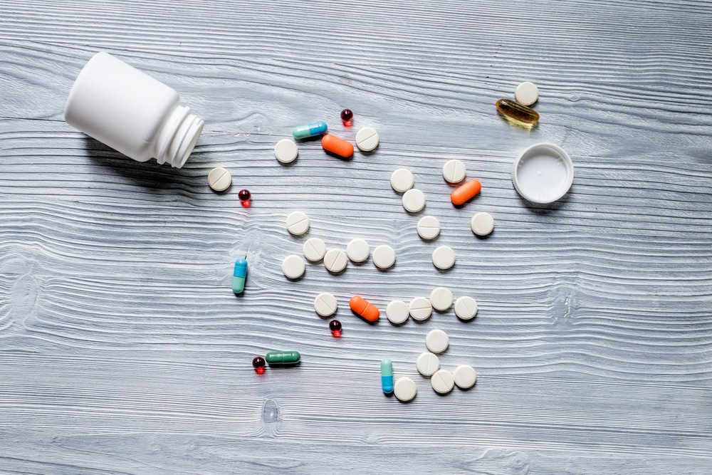 Drug therapy. Pills and pill bottle on grey table background top view