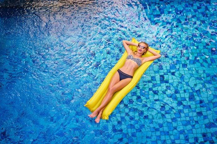 Enjoying suntan. Vacation concept. Top view of slim young woman in bikini on the yellow air mattress in the swimming pool.