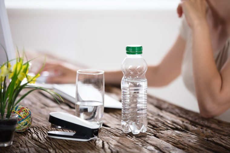 Water Bottle And Drinking Glass On Desk And Woman In Foreground Using Computer