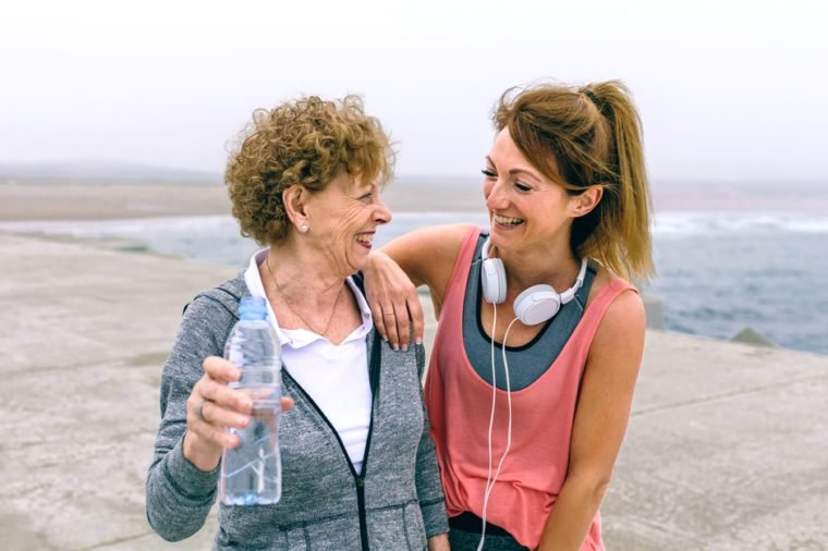 Senior sportswoman laughing with female friend by sea pier