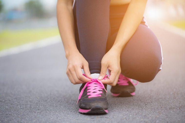 young asian woman tying running shoes