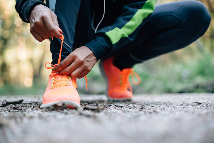 anonymous figure crouching to tie the laces of their sneakers on an outdoor path