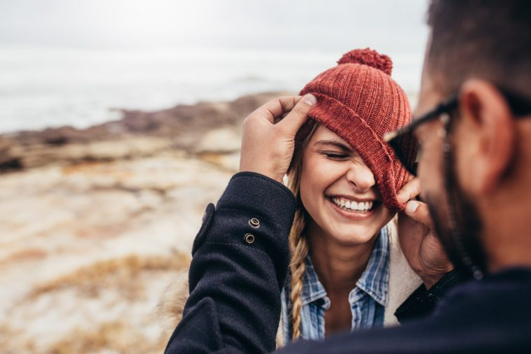 Close up portrait of smiling young couple having fun outdoors. Man and woman enjoying themselves on a winter day at the beach.