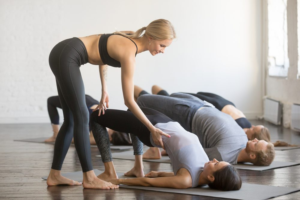 Group of young sporty people practicing yoga lesson with instructor, stretching, doing Glute Bridge exercise, female teacher correcting dvi pada pithasana pose, working out, indoor full length, studio