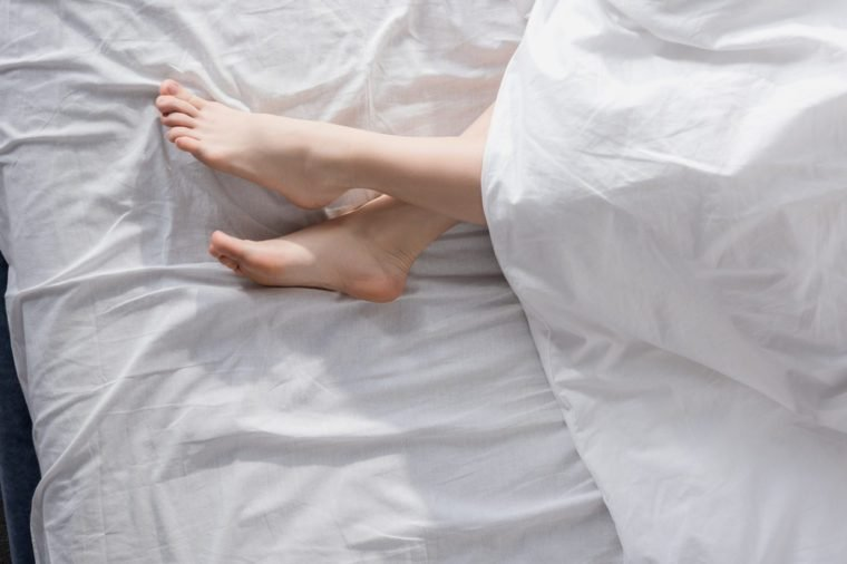 top view of beautiful female feet stretching out of blanket in morning