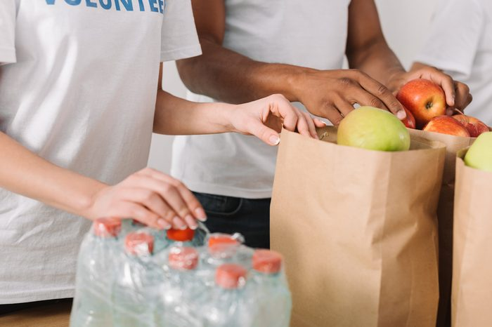 cropped shot of volunteers with apples and water bottles on table