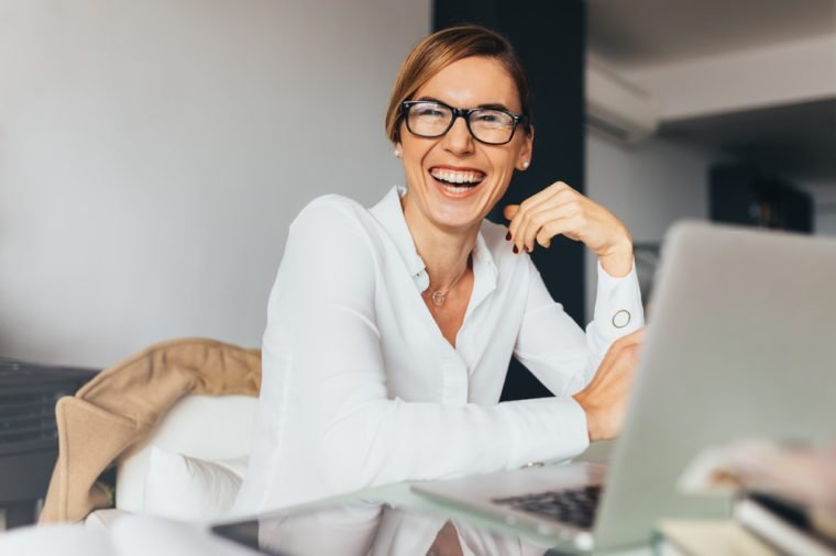 Business woman in spectacles sitting at her desk in office and laughing. Woman sitting in office with laptop computer on her desk.