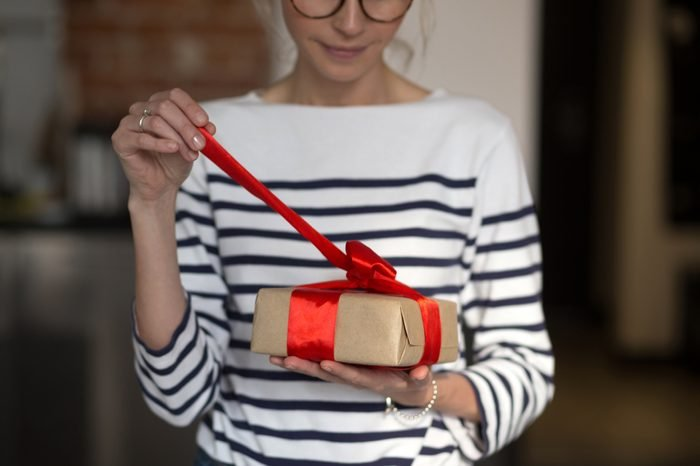 Female hands holding gift box with red ribbon. Woman opening her present. Casual style.