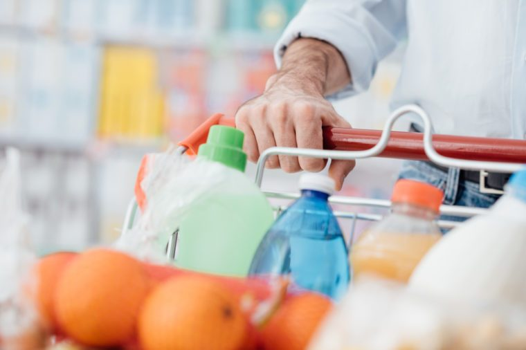 Man doing grocery shopping at the supermarket, he is pushing a full trolley, hand detail close up
