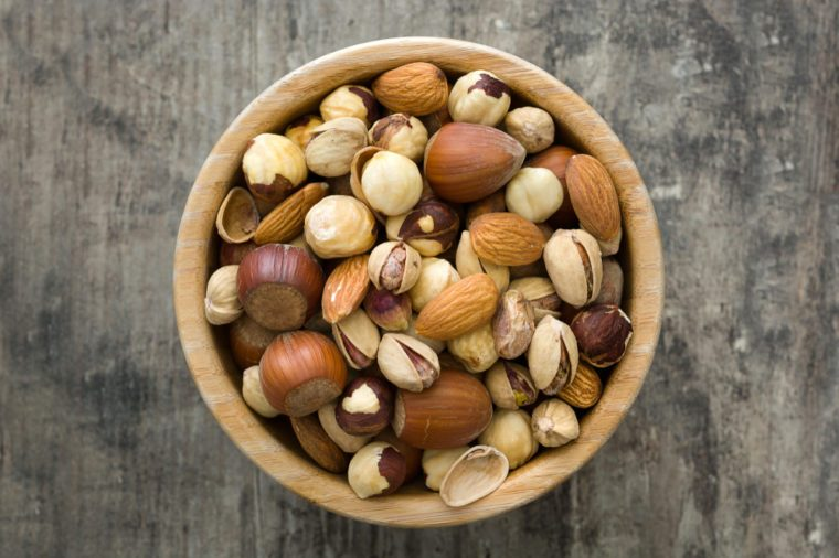 Assorted mixed nuts in bowl on wooden table. Top view