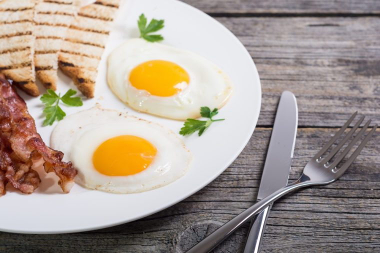Breakfast with eggs bacon and toasts . Food background