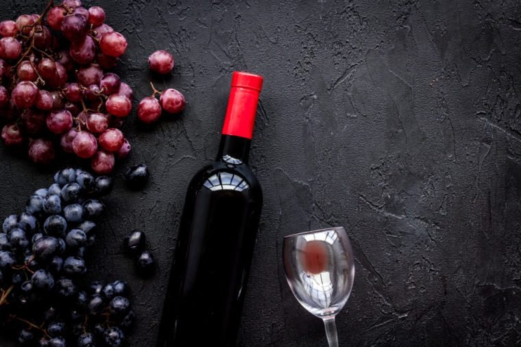 Taste red wine. Bottle of red wine, glass and black grape on black stone background top view copyspace