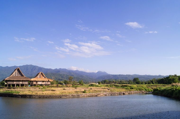 A scenic of view of the local landscape in Bagac, Bataan, Philippines. Two wooden houses stand along a river. Mountains surround the area.