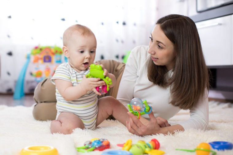 Funny baby boy and young woman playing in nursery. Happy family having fun with colorful toys at home.