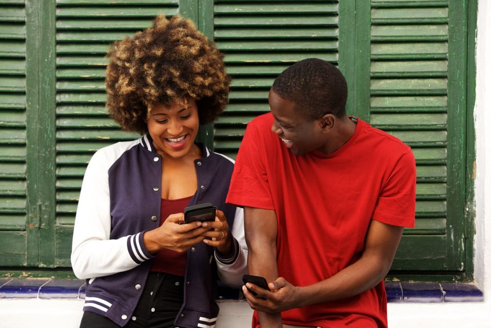 Portrait of laughing couple standing together with mobile phone