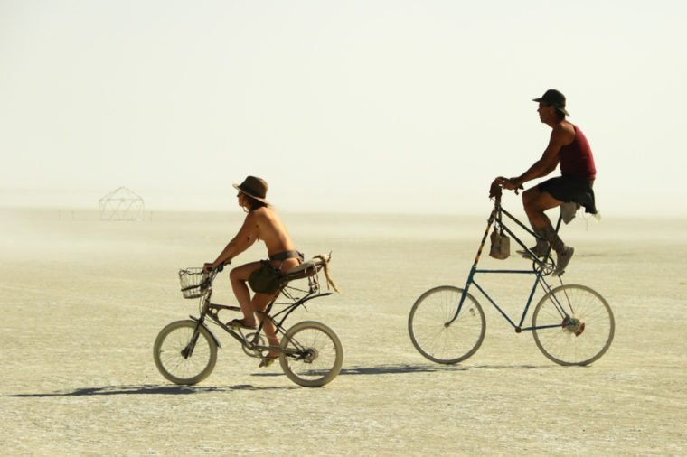 BLACK ROCK CITY, NEVADA - SEPTEMBER 4: Unidentified couple ride on unique bicycles at the Burning Man festival on September 4, 2011 in Black Rock City, Nevada, USA.