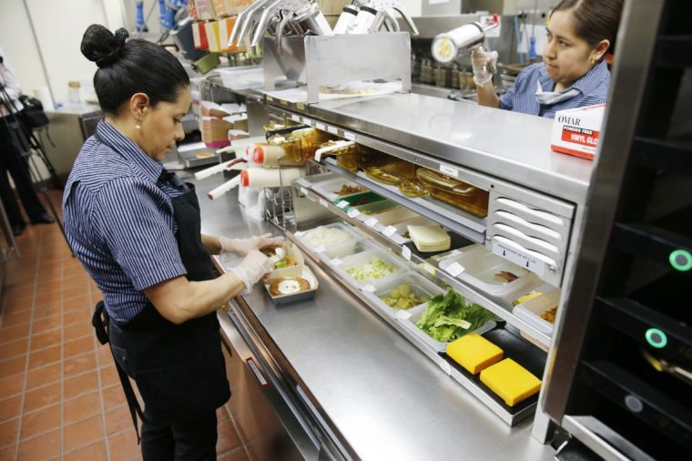 Silvia Ruiz prepares a specialty sandwich at a McDonald's restaurant in Chicago. The company that helped define fast food is making supersized efforts to reverse its fading popularity and catch up to a landscape that has evolved around it. McDonald's is still trying to shake its image for serving junk food and has made a high-profile pledge to offer healthier options
