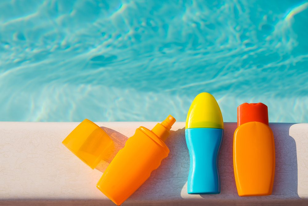 Bottles of sunscreen cream and lotion near swimming pool