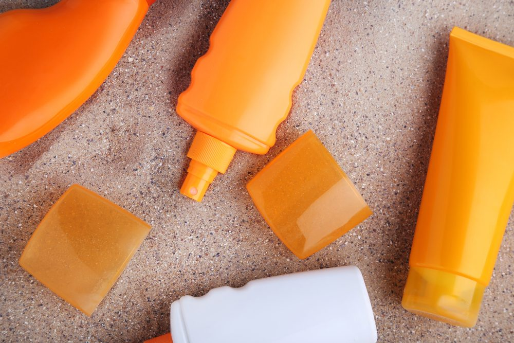 Sunscreen bottles on beach sand