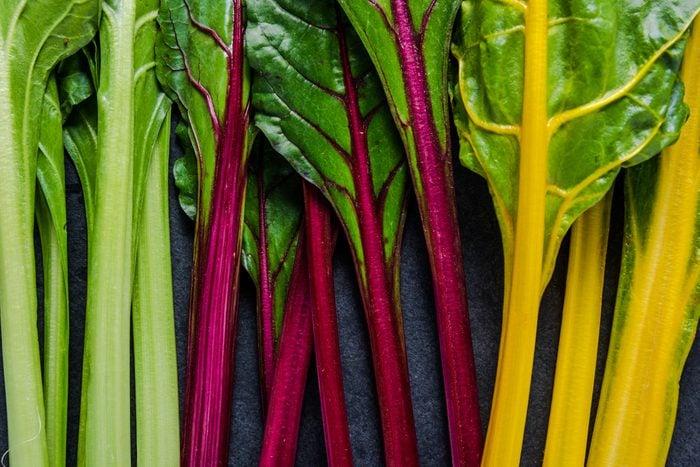 Swiss rainbow chard, vibrant vegetable. Flat lay, from above on dark slate.